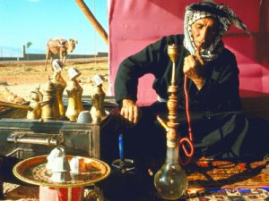 Tribal nomad smoking a hookah in the desert.
