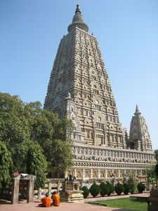 The Mahabodhi temple in Bodhgaya, India, constructed by Ashoka. Two monks are meditating in front of it. The tree under which the Buddha attained enlightenment is on the left, behind the monks. This temple is the number 1 pilgrimage site of Buddhism in the world.  Source: Wikicommons.