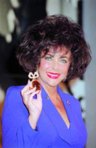 "Elizabeth Taylor poses with a $100,000 special edition bottle of her ""White Diamonds"" fragrance in New York in 1991. Photo: AP via Chicago Sun Times."